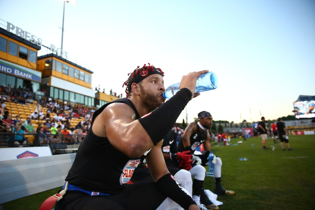 The Money Team's Frankie Solomon rehydrates during a semifinal game against Code Red at the American Flag Football League (AFFL) U.S. Open of Football tournament, Sunday, July 8, 2018 in Kennesaw, Ga. (Kevin D. Liles/AP Images for American Flag Football League)