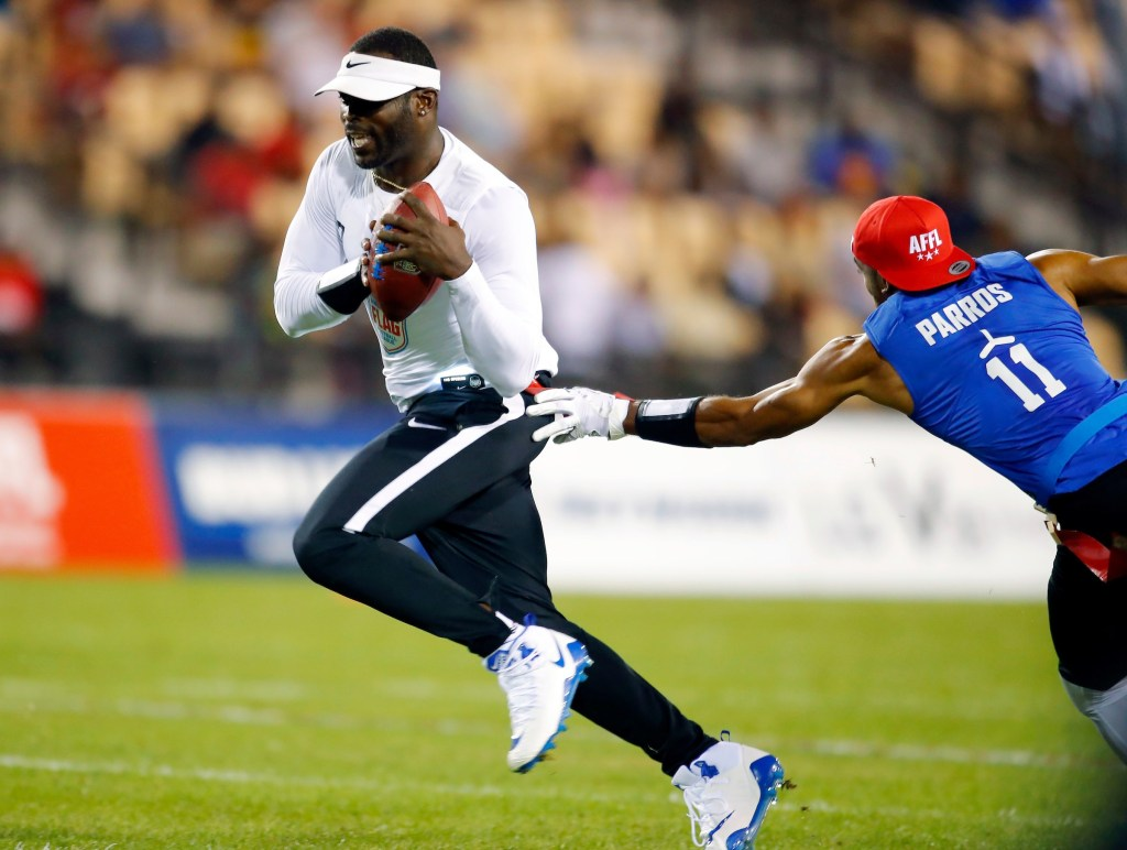 Ocho's Clayton Parros, right, reaches for the flag of Roadrunners' Michael Vick during a semifinal game against Ocho during the American Flag Football League (AFFL) U.S. Open of Football tournament, Saturday, July 7, 2018 in Kennesaw, Ga. (Todd Kirkland/AP Images for American Flag Football League)